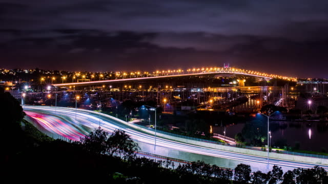 cars in motion on a lighted bridge and highway over the sea with anchored sailing boats at marina video