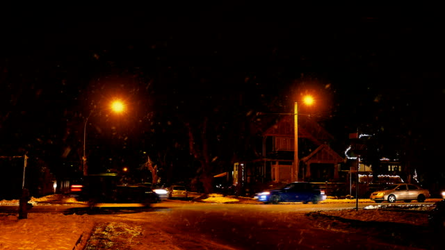 Cars Passing Houses At Night In Snowfall video