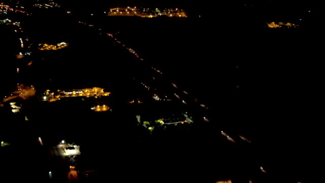 AERIAL: Cars traveling along busy highway through residential zone at night video