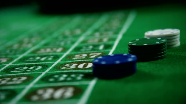 Casino chips and dice on roulette in casino 4k video