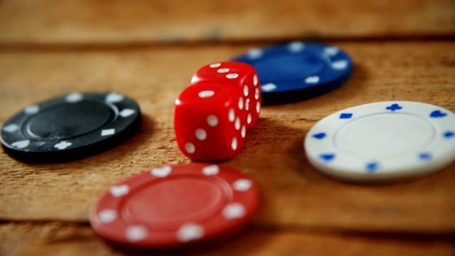 Casino chips and dice on wooden table in casino 4k video