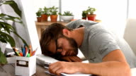 Casual businessman sleeping on desk video