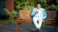 Casual businessman texting on phone on park bench on a sunny day video