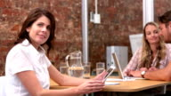 Casual businesswoman smiling at camera using tablet pc video