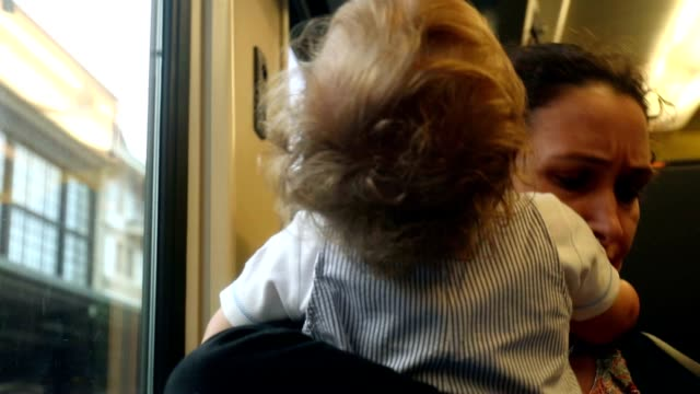 Casual candid shot of mother and baby together on train. Mom kissing tired exhausted baby from commute. Baby wanting to sleep video