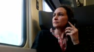 Casual candid shot of woman talking on her cellphone while commuting by train. Woman resolving work issues while traveling by train video