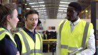 Casual conversation between staff in warehouse, shot on R3D video