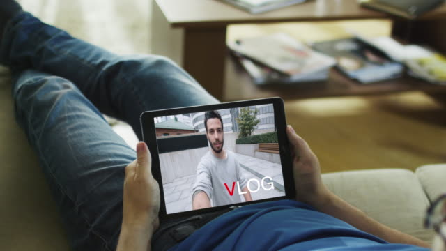 Casual Man Lying on His Couch Watching Fashionable Video Blogg on His Tablet Computer. Inscription 'Vlog' appears on the Screen. video