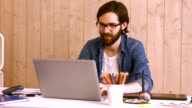 Casual worker at his desk using laptop video