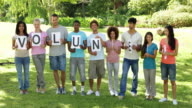 Casual young friends holding letters spelling volunteer video