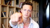 Casual young man pointing a finger towards camera video