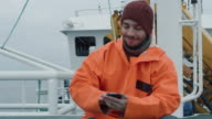 Casualy Dressed Fisherman Using Mobile Phone while Traveling on Ship. video