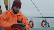 Casualy Dressed Fisherman Using Tablet Computer with Navigation Maps while Traveling on Ship. video
