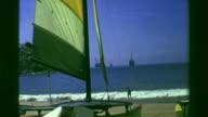 1978: Catamaran sailboat beached on blue sky paradise day. video