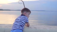 Caucasian boy in a striped vest on the waterfront. Joyful in the background yachts, sunset. video
