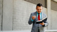 Caucasian businessman stand with notepad outdoors video