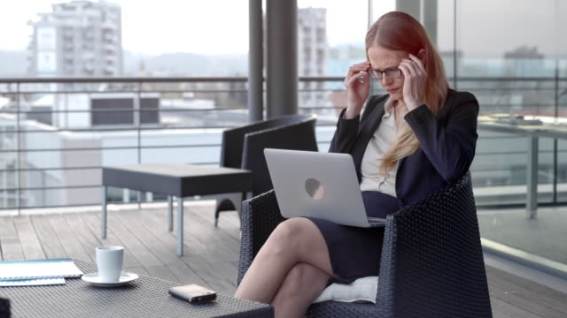 Caucasian businesswoman pondering while working on her laptop in the terrace lounge overlooking the city video