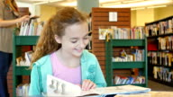 Caucasian elementary age home school girl reads a picture book in local library video
