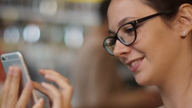 Caucasian Ethnicity Smiling Young Woman using Mobile Phone at Cozy Coffee Shop. video