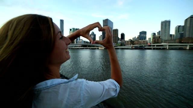 Caucasian female makes heart shape finger frame to Brisbane video