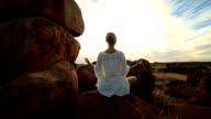Caucasian female on spheric boulder exercises yoga video