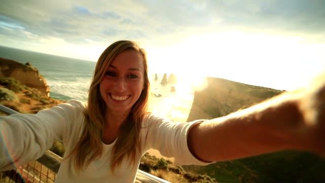 Caucasian female takes selfie portrait at the Twelve Apostles, Australia video