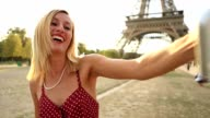 Caucasian female takes selfie portrait in Paris using mobile phone video