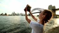 Caucasian female uses digital tablet to photograpgh Sydney skyline video