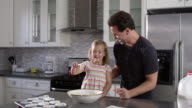 Caucasian girl and dad have fun preparing cake mix mix, shot on R3D video