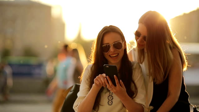 Caucasian girls making selfie background soft sunset light. Young tourist friends enjoy weekend outdoors smiling happy video
