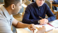 Caucasian high school freshman studying in library with African American senior tutor video