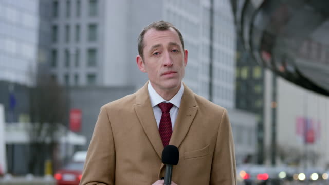 Caucasian male reporter reporting live from the business district video