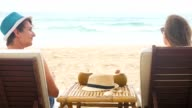 Caucasian man and woman in love sitting in beach chairs on a sea shore and drinking fresh coconut water video