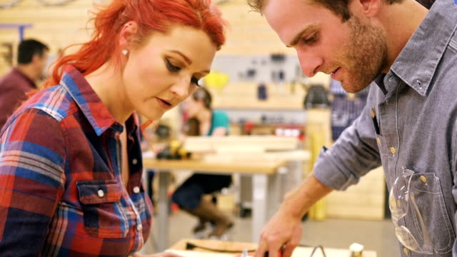 Caucasian man and woman work together marking measurements on wood in community workshop video