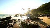 Caucasian man arms outstretched on the beach at sunrise video