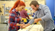 Caucasian man teaches Caucasian woman about woodworking in community workshop video