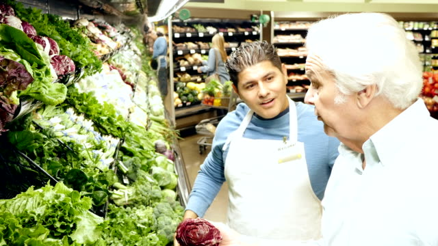 Caucasian senior adult man is getting advice about produce from mid-adult Hispanic male supermarket employee video