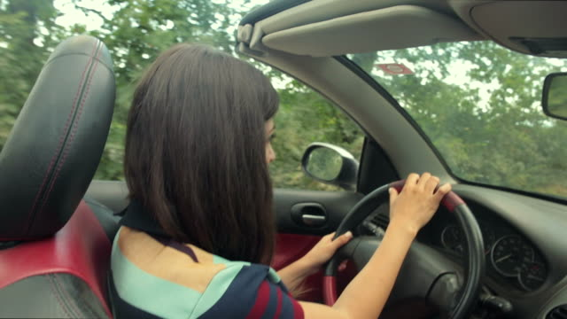 Caucasian woman experiencing freedom in a convertible car. video