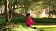 Caucasian woman meditating in a green park video