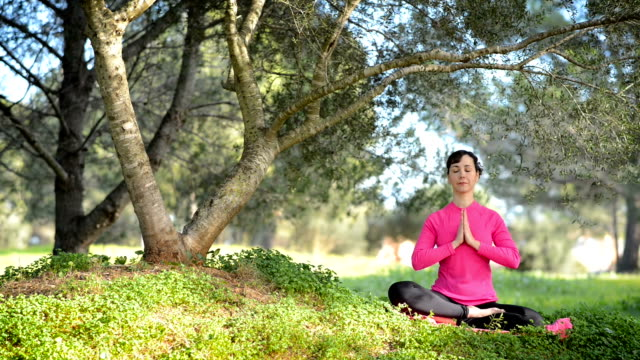 caucasian woman practicing meditation in the park video