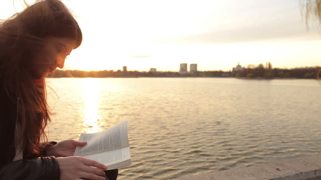 Caucasian woman reading a book in the park. video