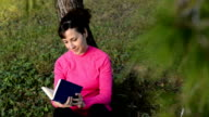 caucasian woman reading book in the park video