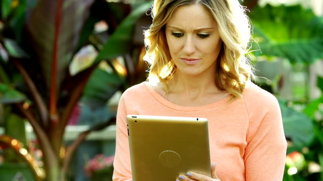 Caucasian woman shops for flowers at greenhouse using tablet video