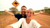 Caucasian young couple take selfie portrait with kangaroo crossing sign video