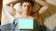 Caucasian young man sleeps. A tablet PC lays on him (green screen) video