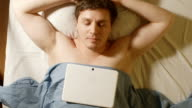 Caucasian young man sleeps and a tablet PC lays on him video