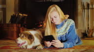 Caucasian young woman lying by the fireplace, enjoy the tablet. Next to her is a dog video