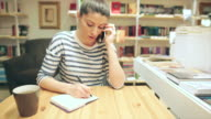 Caucasian young woman talking on the phone and writing notes. video