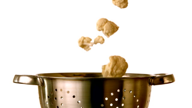 Cauliflower falling into colander on white background video