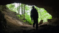 Caver Exits Dark Cavern into Lush Forest video